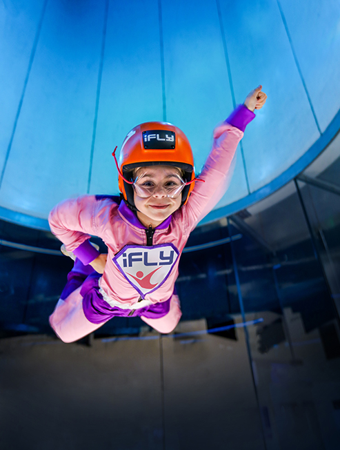 Girl dressed in a cape flying at iFLY Gold Coast